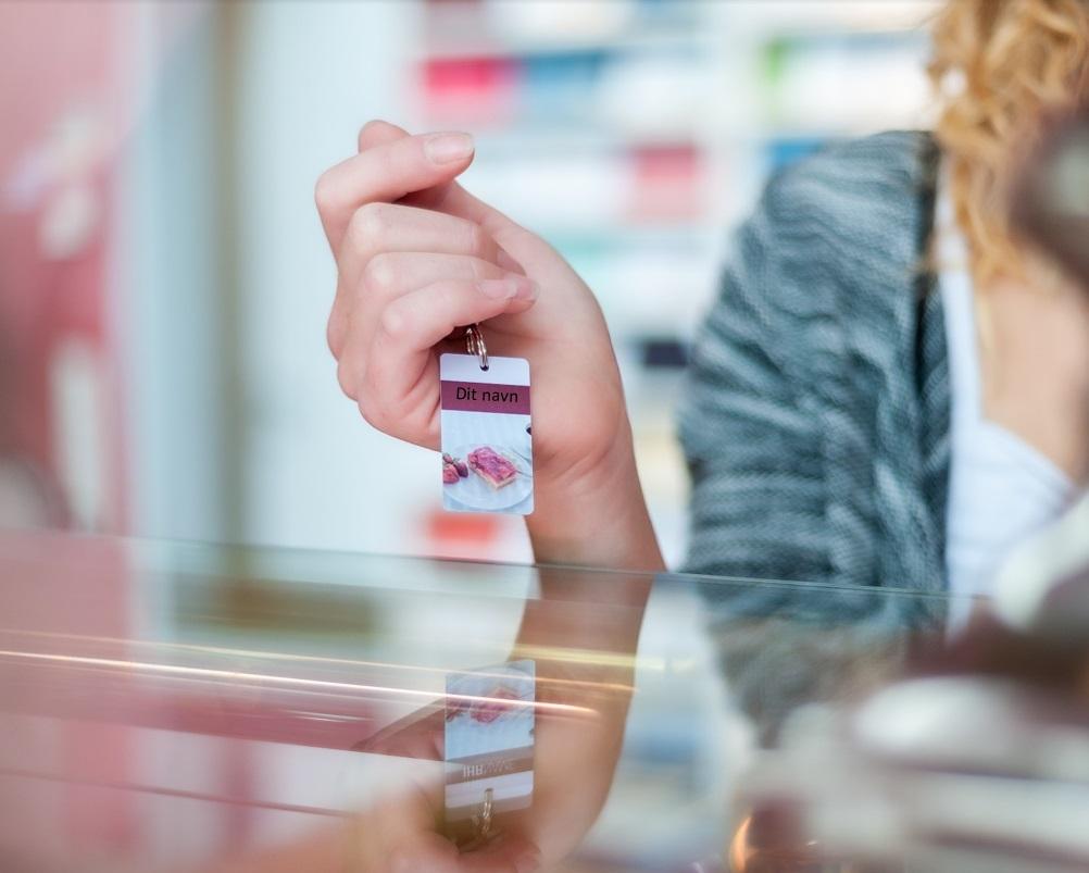 Kvinde fremviser sin nøglebriks til Vectron POS loyalitetssystem